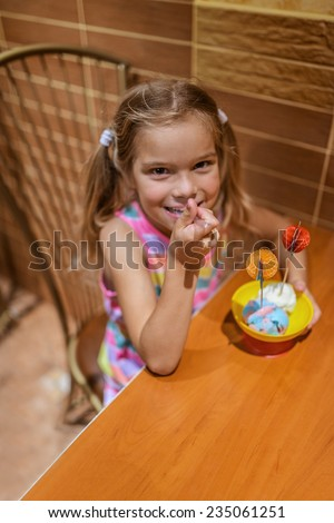 Beautiful little smiling girl sits at table in cafe and eating ice cream. - stock photo