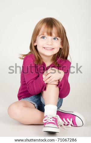 beautiful little smiling girl sitting on the ground - stock photo