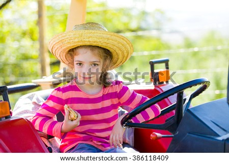 Beautiful little village girl eating on the tractor on fields. - stock photo