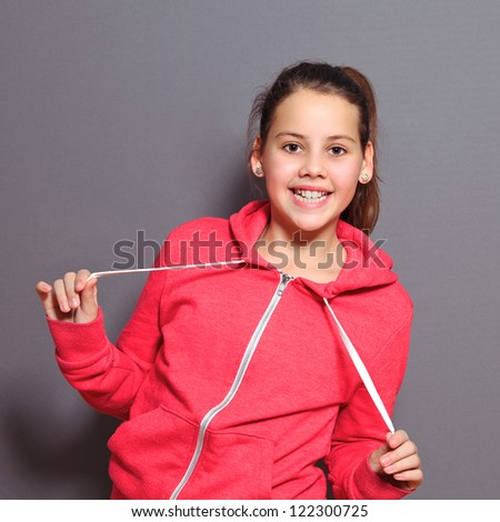 Beautiful litttle girl with a lovely smile posing in a pink top looking at the camera , studio half body portrait on grey - stock photo