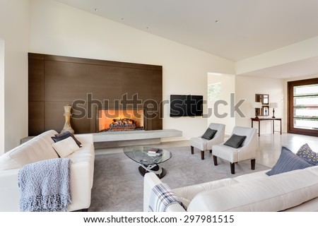 Beautiful living room in luxury home with fireplace, tv, couches, and entry - stock photo