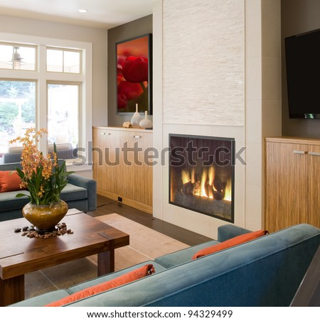 Beautiful Living Room in New Home with Fire in Fireplace - stock photo