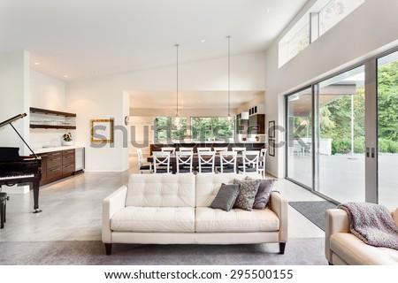 Beautiful living room in new luxury home with couch, piano, sliding glass doors leading out to backyard patio, huge dining room table, pendant lights, vaulted ceilings, wet bar, and kitchen - stock photo
