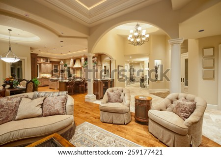Beautiful living room in new luxury home with view of kitchen, high end amenities, and hardwood floors - stock photo