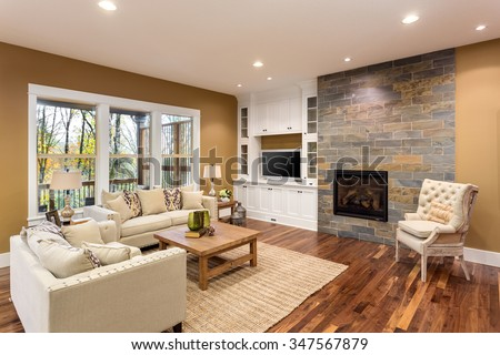 Beautiful living room interior with hardwood floors and fireplace in new luxury home - stock photo
