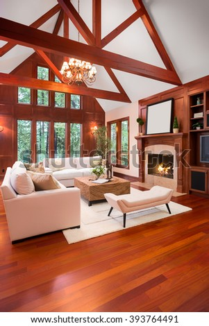 Beautiful living room interior with hardwood floors and fireplace in new luxury home. Includes built-ins with television and vaulted ceilings. - stock photo