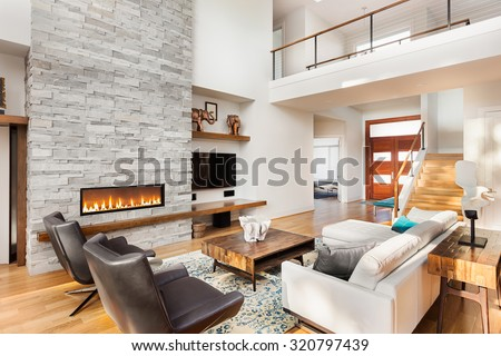Beautiful living room interior with hardwood floors and fireplace with roaring fire in new luxury home. Includes view of entry and front door. - stock photo