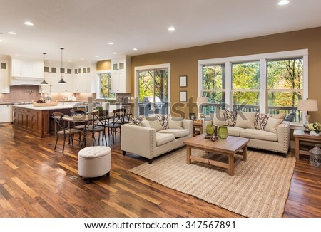 Beautiful living room interior with hardwood floors and view of kitchen in new luxury home - stock photo