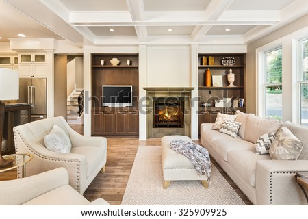 Beautiful living room interior with hardwood floors, coffered ceiling, and roaring fire in fireplace, in new luxury home