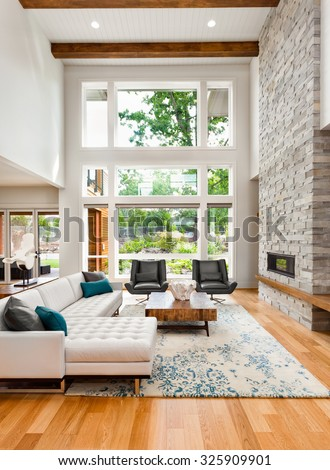 Beautiful living room interior with hardwood floors, huge bank of windows, tall vaulted ceiling, and fireplace in new luxury home - stock photo
