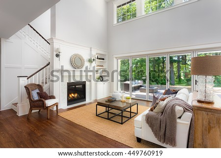 Beautiful living room interior with hardwood floors, vaulted ceilings, sliding glass doors, and fireplace in new luxury home