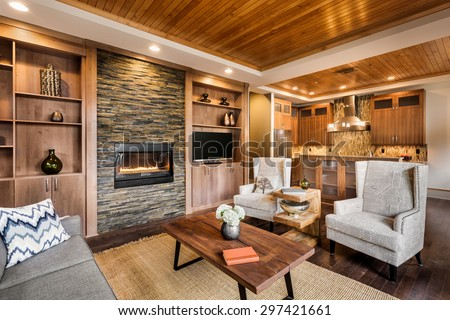 Beautiful living room with hardwood floors, ceiling, and fireplace in new luxury home. Includes view of kitchen and hardwood cabinets - stock photo