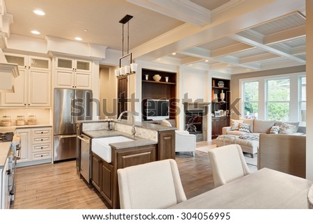 Beautiful living room with hardwood floors, fireplace and couch in new luxury home; view of kitchen - stock photo