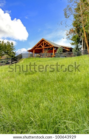 Beautiful log cabin on the hill with green fresh grass. - stock photo