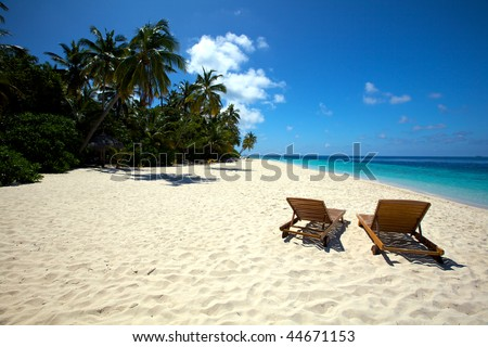 Beautiful lonely beach with chairs - stock photo