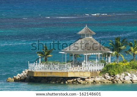 Beautiful lonely gazebo surrounded by the ocean. - stock photo