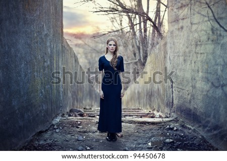 beautiful lonely girl  in long dress near gloomy tunnel on sunset - stock photo