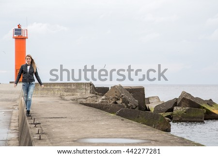 Beautiful lonely girl walking by the sea with a lighthouse on the background. - stock photo