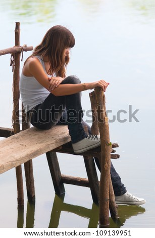 Beautiful lonely teenage girl sitting on the river dock and touching the water with her foot. - stock photo