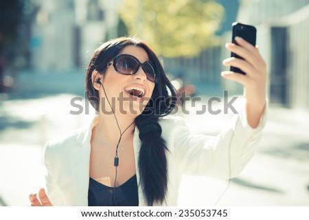 beautiful long black hair elegant business woman using smartphone  in the city - stock photo