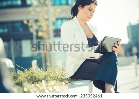 beautiful long black hair elegant business woman using tablet in the city - stock photo