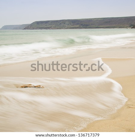 Beautiful long exposure image of golden sand beach at sunset - stock photo