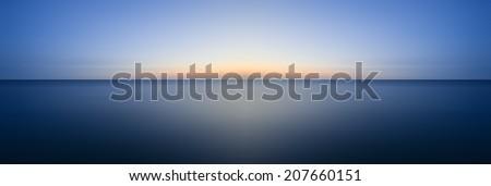 Beautiful long exposure seascape image of calm ocean at sunset - stock photo