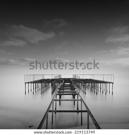 Beautiful long exposure seascape shot with clouds and old metal pier. Photo take in black and white. Odessa, Ukraine - stock photo
