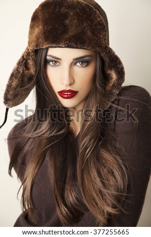 beautiful long hair brunette wearing fashion cap, studio portrait