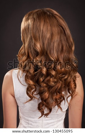 Beautiful long hair Brunette woman with healthy curly dark Hair and stylish hairstyle. Teenager girl beauty model. fashion lady with long curly glossy hairs at studio. Health and beauty products