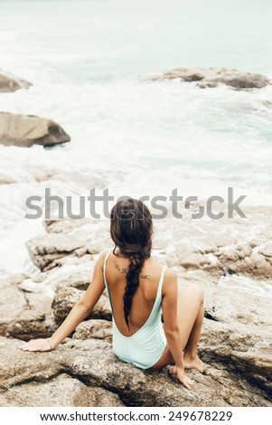 Beautiful long hair female model wearing bikini, posing on a rock with waves crashing nearby, outdoor portrait