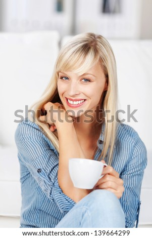 Beautiful long haired blonde woman relaxing on the sofa at home with a cup of coffee giving the viewer a lovely smile