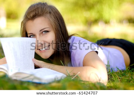 Beautiful long haired brunette female student having fun with book outdoors - stock photo