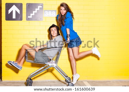 beautiful long haired girl in jeans mini skirt rides a boy in hat on shopping trolley in front of yellow brick wall - stock photo