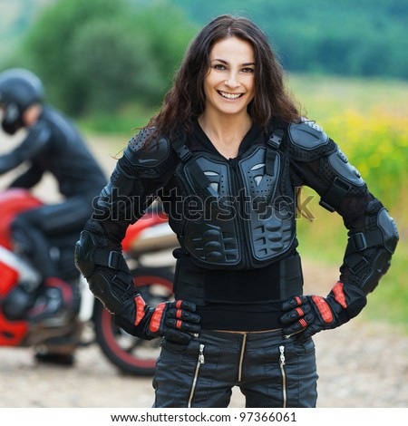 Beautiful long-haired skinny woman standing background guy riding motorcycle road