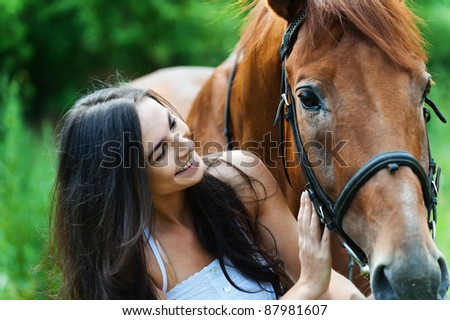 beautiful long-haired woman standing next horse
