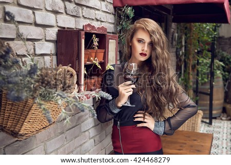 Beautiful long hairl woman with glass red wine - stock photo