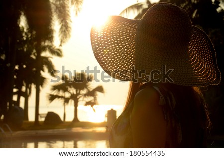 Beautiful long hairs lady in long dress and big beach hat on her morning relax vacation. - stock photo