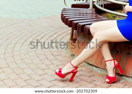 beautiful long legs girl in red shoes in blue dress sits in the city - stock photo