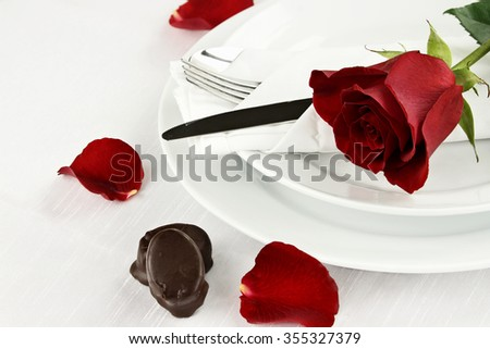 Beautiful long stem red rose across an empty dinner plate setting with chocolate candy. Shallow depth of field. - stock photo