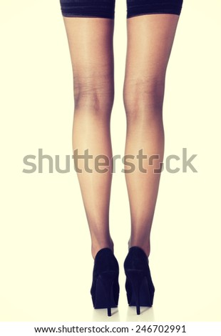 Beautiful long woman's legs in stockings and black high heels.  - stock photo
