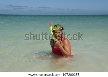 Beautiful looking mature woman in red bathers and yellow snorkel gear, swimming in shallow water of tropical beach, isolated with ocean and blue sky as background and copy space. - stock photo