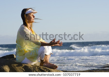 Beautiful looking mature woman is sitting relaxed and happy meditating at the ocean, isolated with wild sea and blue sky as background and copy space. - stock photo