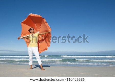 Beautiful looking senior woman standing happy and cheerful with big orange umbrella at beach enjoying retirement, isolated with ocean and blue sky as background and copy space.