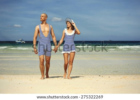 Beautiful  love couple in swimsuit on the beach. Happy travellers on blue sea