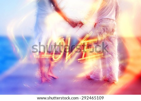 Beautiful love couple standing barefoot holding hands on a jetty by the sea in the Maldives with a dreamy surreal effect and word - Love - in fiery letters, symbolic of romance and commitment - stock photo