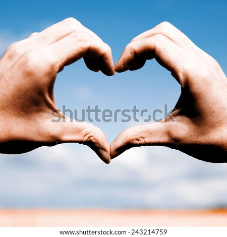 Beautiful Love shape hands - heart on yellow field and blue sky - stock photo
