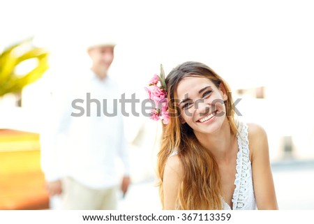Beautiful lovely blonde woman with flower hair accessory on the street on a sunny day - stock photo