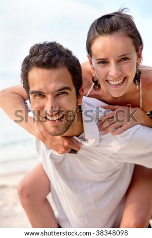 Beautiful loving couple at the beach smiling