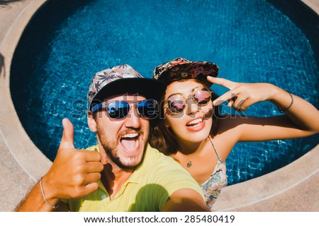 beautiful loving couple in bright sun glasses and caps baseball caps make selfi on the background of the pool